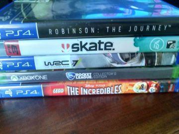 a picture of the cases of five video games: Lego The Incredibles (PS4), Rocket League (Xbox), WRC (PS4), and Robinson: The Journey (PS4). Not pictured, but reviewed in post: Lego Lord of the Rings video game