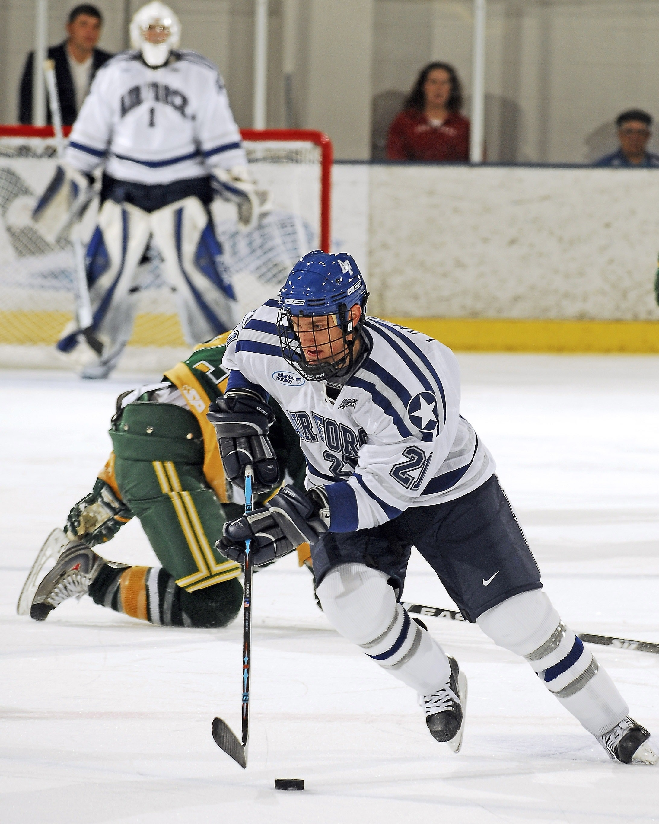 a hockey player in a white and blue uniform pushes a puck across the ice, while a hockey player in a green and yellow uniform stumbles behind him