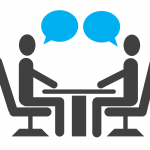 two stick figures seated at a table facing each other, with empty speech bubbles above both their heads