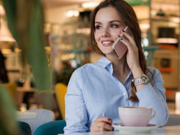 Woman talking on a cell phone in a cafe