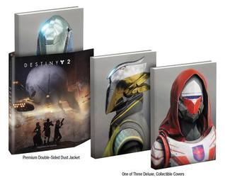 """Destiny 2 Collector's Edition Guide"" showing three versions of the large, hardbound book: one with a slipcover showing a large metal planet hovering over 3 armed people, and two without showing characters from the game, one with white and red armor, and the other with gray and yellow."