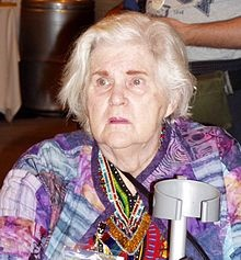 A picture of Ann McCaffrey in her later years, seated, with white hair, a multi-color jacket, and a cane.