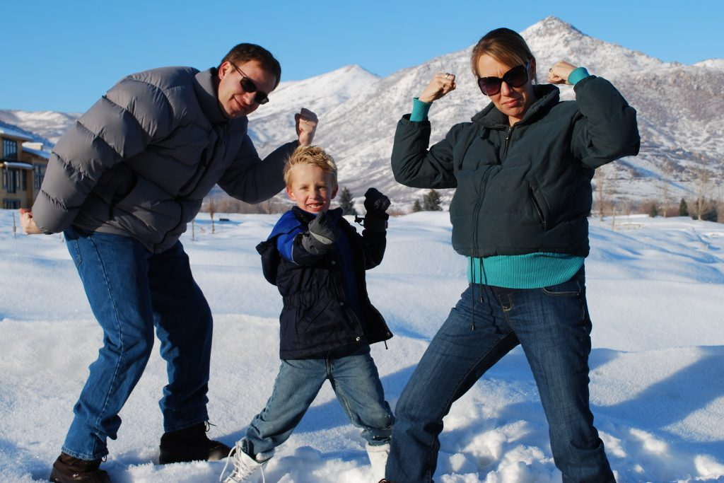 """a husband, wife, and five-year-old son making """"strong"""" poses in the snow."""